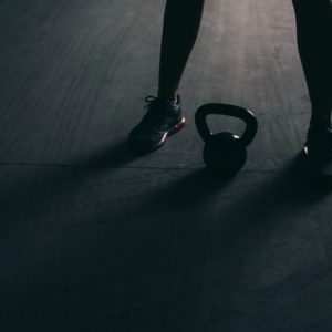 Legs of a bodybuilder with a kettlebell lying between them on a concrete floor